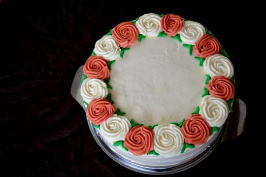 Eine schlichte Hochzeitstorte, gefüllt mit einer Mascarponecreme und Erdbeeren, und einer Schokoladencreme mit Schokoladenraspeln. Schlicht gehalten mit roten und weißen Rosen dekoriert.