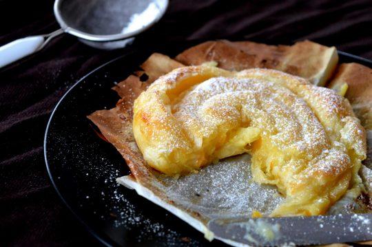 Die Blätterteigschnecke besteht aus zusammengerollten Blätterteigstreifen gefüllt mit Vanillecreme und Pfirsichen.