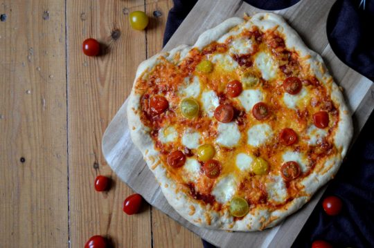Einfache Pizza mit Mozzarella, Cheddar und Tomaten
