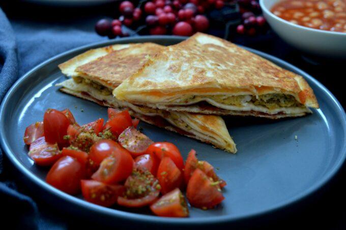 Frühstückswrap gefüllt mit Rührei, Bacon, Käse und Tomatensalat