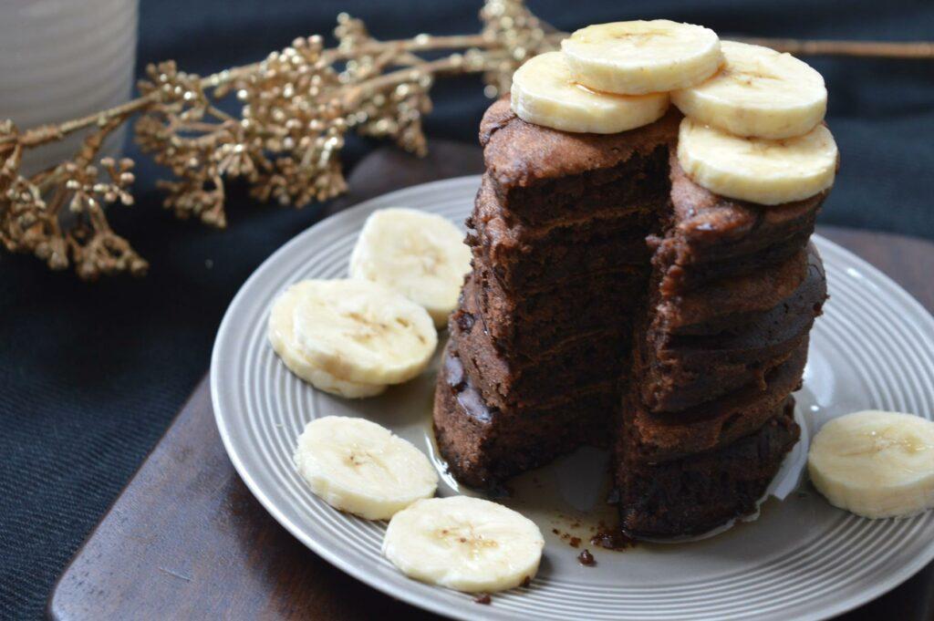 Leckeres Frühstück Schoko-Pancakes gestapelt mit Bananenscheiben oben drauf